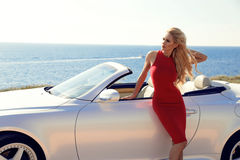 Woman with blond hair in red dress posing beside luxury auto Royalty Free Stock Images