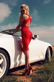 Woman with blond hair in red dress posing beside luxury auto Royalty Free Stock Image