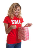 Woman with blond hair and shopping bag in a sales-shirt. On an isolated white background for cut out Royalty Free Stock Photo