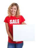 Woman with blond hair and a signboard in a sale shirt