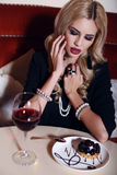 Woman with blond hair sitting in cafe with glass of wine and dessert Royalty Free Stock Photo