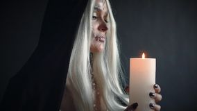 Woman with blond hair with skull and black cloak holding burning candle. Mystical video in Gothic style, woman with blond hair with sweet white skull and black stock video footage