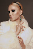 Woman with blond hair and smokey eyes makeup,wears luxurious fur coat Royalty Free Stock Image