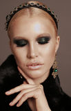 Woman with blond hair and smokey eyes makeup,wears luxurious fur coat Stock Image