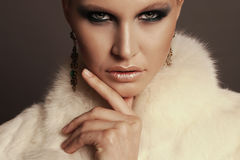 Woman with blond hair and smokey eyes makeup,wears luxurious fur coat Stock Photo