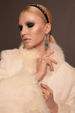 Woman with blond hair and smokey eyes makeup,wears luxurious fur coat Royalty Free Stock Photo