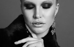 Woman with blond hair and smokey eyes makeup,wears luxurious fur coat. Fashion photo of glamour beautiful woman with blond hair and smokey eyes makeup,wears Stock Photo