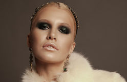 Woman with blond hair and smokey eyes makeup,wears luxurious fur coat. Fashion photo of glamour beautiful woman with blond hair and smokey eyes makeup,wears Royalty Free Stock Photos