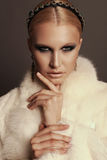 Woman with blond hair and smokey eyes makeup,wears luxurious fur coat. Fashion photo of glamour beautiful woman with blond hair and smokey eyes makeup,wears Stock Images