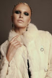 Woman with blond hair and smokey eyes makeup,wears luxurious fur coat Royalty Free Stock Images