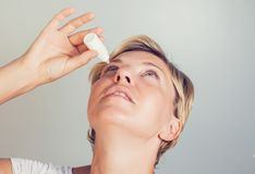 A woman using eye drops in eyes royalty free stock images