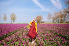 Woman with blond hair wearing a red dress and yellow blouse holding a basket with tulips flowers royalty free stock images