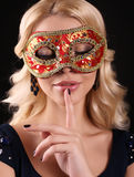 Woman with blond hair, wears elegant black dress and carnival mask Stock Image