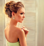 Woman with blond hair, wears in a wedding gown. Young beautiful woman, dressed in evening gown and  openwork earings. Example of wedding hairstyle for blond Royalty Free Stock Photos