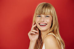 Woman. Blond woman laughing in red studio, portrait Stock Photos