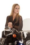 Woman blond sit motorcycle clow look side. A close up of a woman sitting on her motorcycle holding her helmet in her lap looking away royalty free stock image