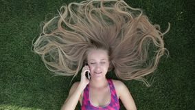 Woman with blonde amazing long hair lying on grass stock video footage