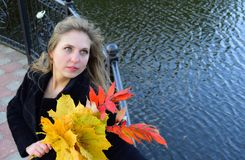 The woman the blonde with blue eyes holds yellow leaves in hand. Woman beautiful and young.The woman is against the background of water Royalty Free Stock Photo