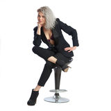 Woman with blonde curly hair in black business suit sits on chai Stock Photo