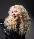 Woman blonde curly hairs, surprised with open mouth black lips,. Beautiful fashion portrait over gray background Royalty Free Stock Image
