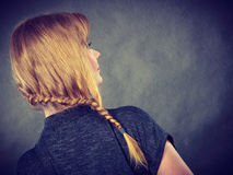 Woman with blonde hair and braid hairdo. Hairstyles and hairstyiling concept. Woman with dark blonde hair and braid hairdo, back view. Studio shot on dark Royalty Free Stock Image