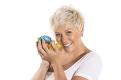 Woman with blonde hair holding chocolate bunny easter egg. Stock Images
