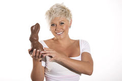 Woman with blonde hair holding chocolate bunny easter egg. Royalty Free Stock Photo