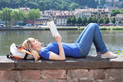 Woman with blonde hair reading a boook at riverside. Beautiful young woman with blonde hair reading a boook at riverside on a sunny summerday Royalty Free Stock Photos