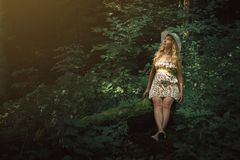 Woman with blonde hair sitting on a tree in the forest. Beautifu Royalty Free Stock Image