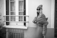 Woman with blonde hair, urban style. Parisian fashion model near house. Look and style. Beauty and fashion. girl in fashionable red dress, hat and glasses Stock Photography