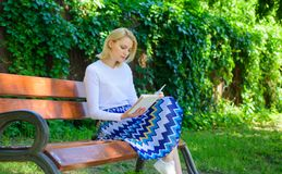 Woman blonde take break relaxing in park reading book. Reading literature as hobby. Books are her passion. Girl keen on. Book keep reading. Girl sit bench royalty free stock photo