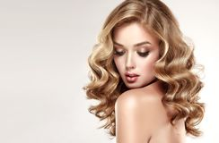 Woman blonde with voluminous, shiny,curly and loose hairstyle. Royalty Free Stock Photography