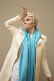 Woman blonde in white coat, blue scarf. Fashion hairstyle, make-up. Stock Photo