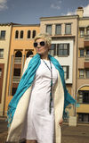 Woman blonde in white dress, coat, blue scarf. Fashion hairstyle. Royalty Free Stock Photo