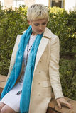 Woman blonde in white dress, coat, blue scarf sitting outdoor. Fashion model shot. Stock Photography