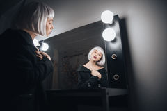 Woman in blonde wig sitting near mirror in dressing room Royalty Free Stock Images
