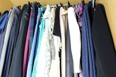 Woman blouse hanging in the closet. Group of blouses hung for a long time, with dust, in the closet royalty free stock photo