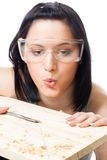 Woman blow away scobs after drilling. From wood plank, isolated Royalty Free Stock Photography