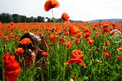 Woman blow bubble in poppy field, dreams, wishes. royalty free stock images