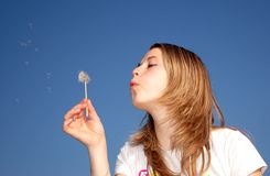 Woman blow a dandelion Royalty Free Stock Images