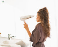 Woman blow drying hair in bathroom Stock Photography