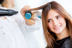 Woman blow drying her hair Stock Images