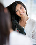 Woman blow drying her hair Royalty Free Stock Photography