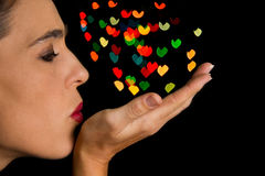 Woman blow heart shape bokeh spots off her hand Royalty Free Stock Photos