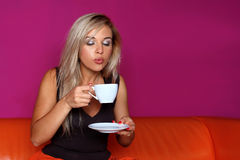 Woman blow to cup of hot drink royalty free stock photography