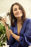 Woman blowdrying her hair Royalty Free Stock Photo