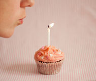 Woman Blowing A Candle On A Pink Cupcake Royalty Free Stock Images