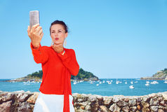 Woman blowing air kiss and taking selfie in front of lagoon Royalty Free Stock Image