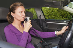 Woman blowing into breathalyzer. Woman in car blowing into breathalyzer Stock Photography
