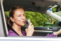 Woman blowing into breathalyzer. Woman in car blowing into breathalyzer Royalty Free Stock Images